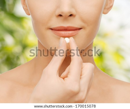 healthcare and medical concept - closeup picture of beautiful woman with pill - stock photo