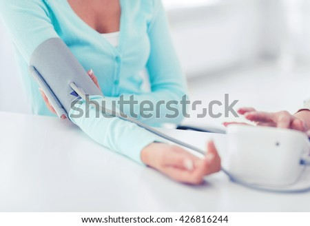 healthcare and medical concept - doctor or nurse with patient measuring blood pressure - stock photo
