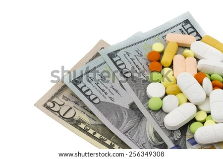Healthcare and medical concept. Heap of different pills, tablets and capsules on banknotes of dollars folded fan isolated on white background  - stock photo