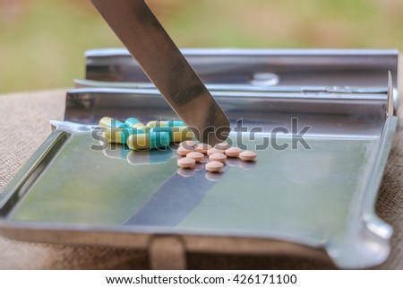 Healthcare and medical concept. Heap of different pills, tablets pouring in the stainless plate