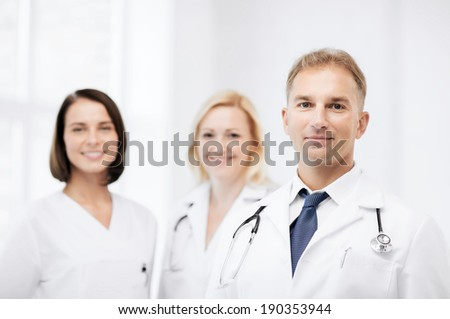 healthcare and medical concept - male doctor with stethoscope and colleagues - stock photo