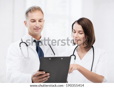 healthcare and medical concept - two doctors discussing diagnosis