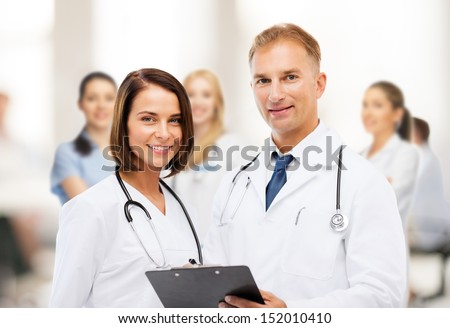 healthcare and medical concept - two doctors with stethoscopes