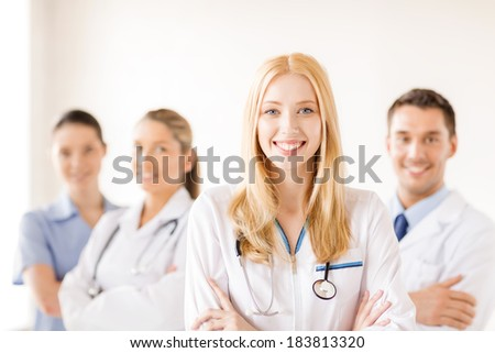 healthcare and medicine concept - attractive female doctor or nurse in front of medical group in hospital - stock photo