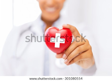 healthcare and medicine concept - female african american doctor holding heart with red cross symbol - stock photo