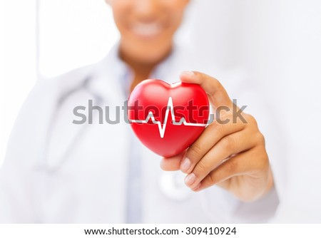 healthcare and medicine concept - female african american doctor holding red heart with ecg line - stock photo