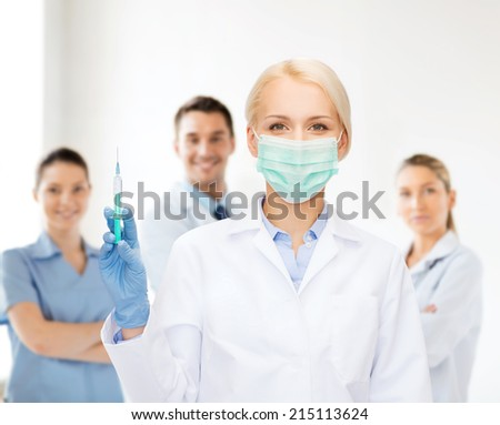 healthcare and medicine concept - female doctor in mask holding syringe with injection - stock photo