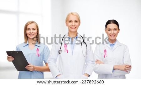 healthcare and medicine concept - female doctors with pink breast cancer awareness ribbon - stock photo