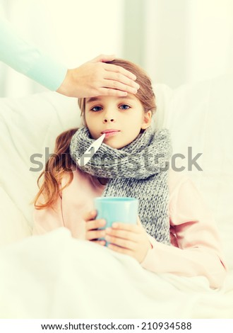 healthcare and medicine concept - ill girl child with thermometer in mouth, cup of hot tea and caring mother - stock photo