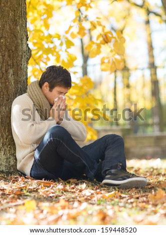 healthcare and medicine concept - ill man with paper tissue in autumn park - stock photo