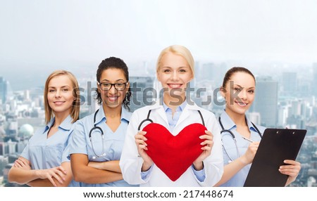 healthcare and medicine concept - smiling female doctor and nurses with red heart - stock photo