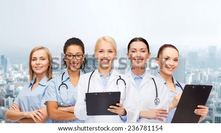 healthcare and medicine concept - smiling female doctors and nurses with stethoscope - stock photo