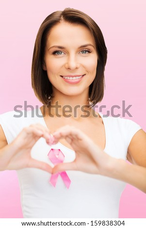 healthcare and medicine concept - woman in blank t-shirt with pink breast cancer awareness ribbon showing heart shape - stock photo