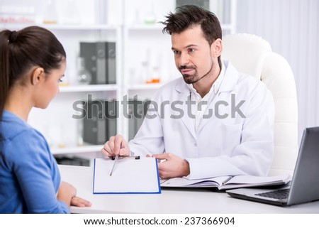 Healthcare and medicine concept. Young male doctor with clipboard and patient in hospital. - stock photo
