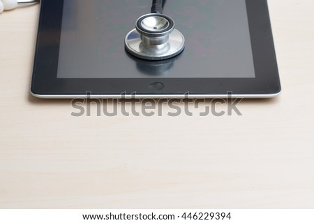 healthcare and technology concept - tablet  and stethoscope