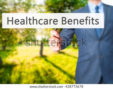 Healthcare Benefits - Businessman hand holding sign. Business, technology, internet concept. Stock Photo - stock photo