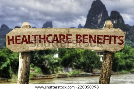 Healthcare Benefits wooden sign with a agricultural background - stock photo