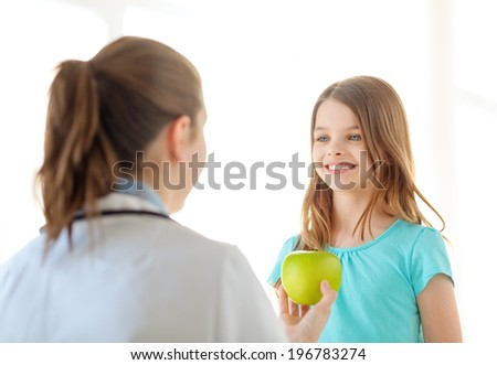 healthcare, child and medicine concept - female doctor giving an apple to smiling little girl - stock photo