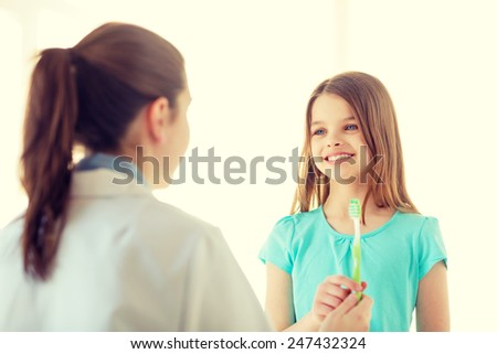 healthcare, child and medicine concept - male doctor giving toothbrush to smiling little girl - stock photo