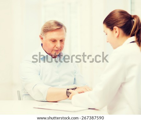 healthcare, elderly and medical concept - female doctor or nurse with male patient measuring blood pressure - stock photo