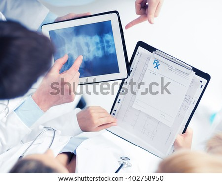 healthcare, hospital and medical concept - group of doctors looking at x-ray on tablet pc - stock photo