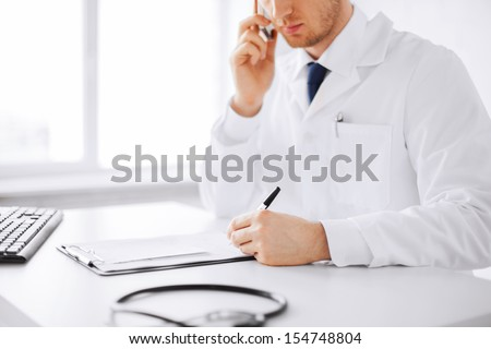 healthcare, hospital and medical concept - male doctor writing prescription paper and capsules - stock photo