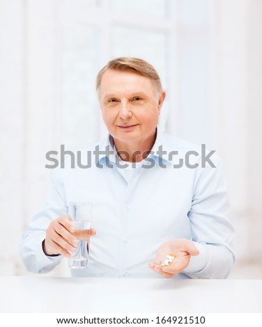 healthcare, madicine, pharmacy and elderly concept - old man with pills and glass of water - stock photo