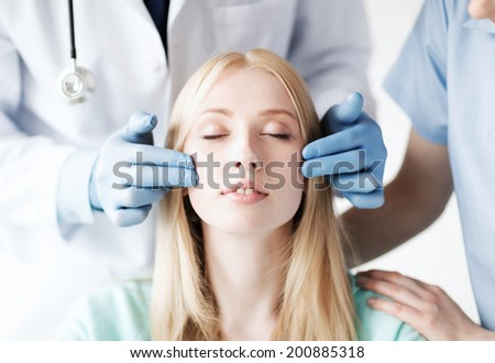 healthcare, medical and plastic surgery concept - plastic surgeon and nurse with patient in hospital - stock photo