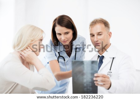 healthcare, medical and radiology concept - doctors with patient looking at x-ray - stock photo