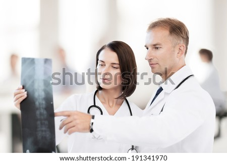healthcare, medical and radiology concept - two doctors looking at x-ray - stock photo