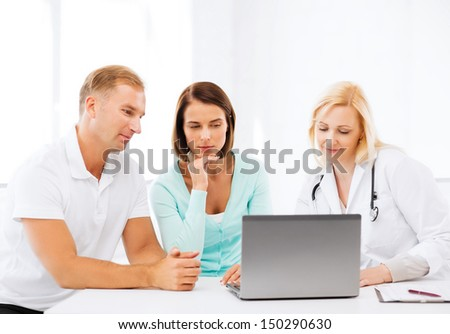 healthcare, medical and technology concept - doctor with patients looking at laptop - stock photo