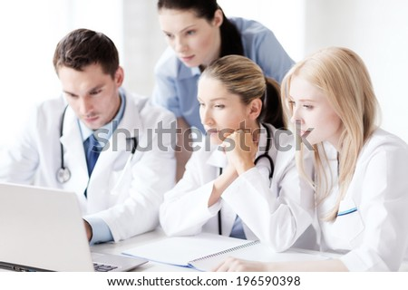 healthcare, medical and technology concept - group of doctors looking at laptop - stock photo