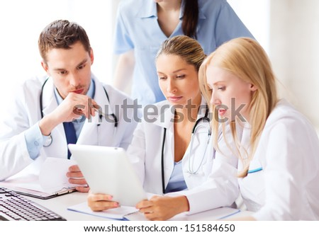 healthcare, medical and technology concept - group of doctors looking at tablet pc - stock photo