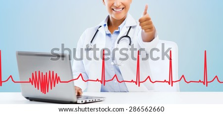 healthcare, medical and technology concept - happy african american female doctor with laptop pc computer showing thumbs up over blue background with red heart shape and cardiogram - stock photo