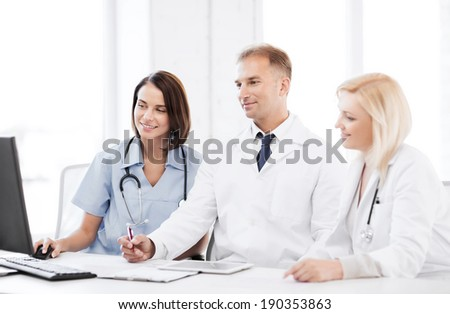healthcare, medical and technology - group of doctors looking at computer on meeting