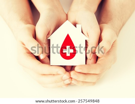 healthcare, medicine and blood donation concept - male and female hands holding hands holding white paper house with red donor sign - stock photo