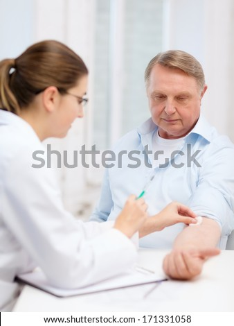 healthcare, medicine and elderly concept - female doctor or nurse doint injection to old man - stock photo