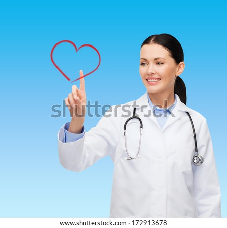 healthcare, medicine and technology concept - smiling female doctor pointing to heart - stock photo