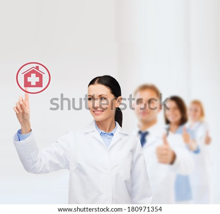 healthcare, medicine and technology concept - smiling female doctor pointing to hospital sign - stock photo