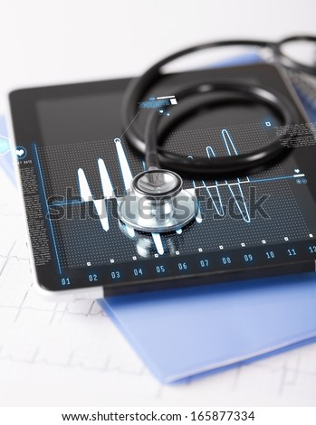healthcare, medicine and technology concept - tablet pc, stethoscope and electrocardiogram - stock photo