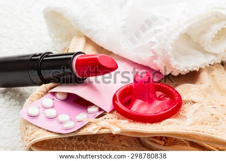 Healthcare medicine, contraception and birth control. Closeup oral contraceptive pills, condom and red lipstick on lace lingerie. - stock photo