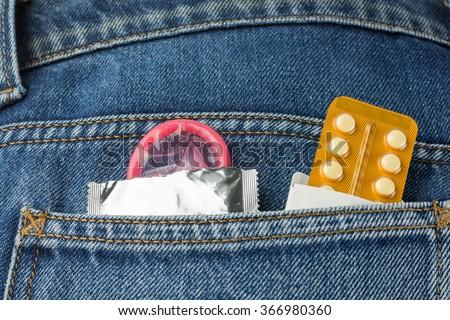 Healthcare medicine, contraception and birth control. Closeup oral contraceptive pills, condom in denim pocket. - stock photo
