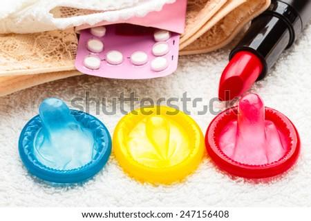 Healthcare medicine, contraception and birth control. Closeup oral contraceptive pills, condoms and red lipstick on lace lingerie. - stock photo