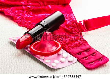 Healthcare medicine, contraception and birth control. Closeup oral contraceptive pills, lipstick and condom with red lace bra lingerie.
