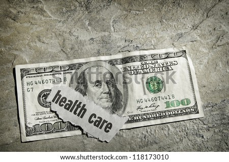 Healthcare newspaper headline on US money - stock photo