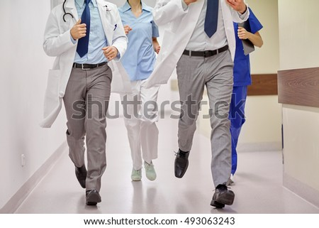 healthcare, people and medicine concept - close up of medics or doctors running along hospital corridor