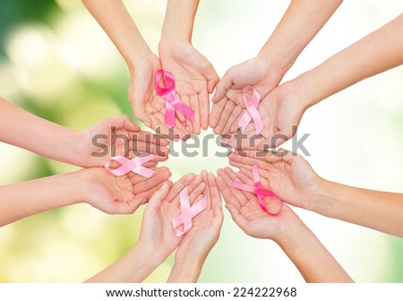 healthcare, people and medicine concept - close up of women hands with cancer awareness ribbons over green background - stock photo