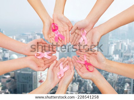 healthcare, people and medicine concept - close up of women hands with cancer awareness ribbons over city background