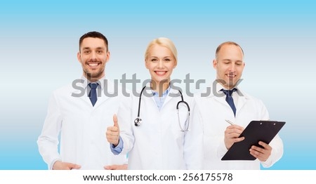 healthcare, people and medicine concept - group of doctors with stethoscope and clipboard showing thumbs up over blue background - stock photo
