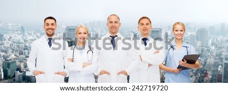 healthcare, people and medicine concept - group of doctors with stethoscopes and clipboard over city background - stock photo